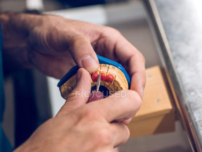 Зубной техник полирует зубы — стоковое фото