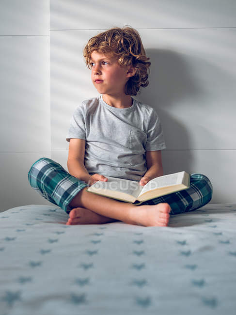 Boy sitting on bed with book — Stock Photo