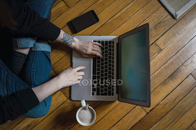 Female hands typing on laptop on floor — Stock Photo