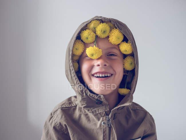 Мальчик с цветами в капюшоне — стоковое фото