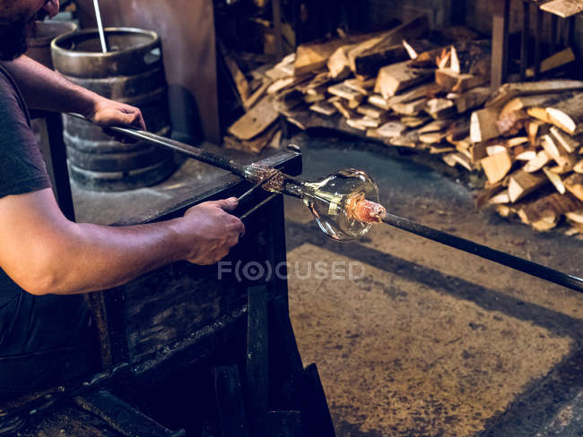 Cropped view of unrecognizable glassblower making glass vase on factory. — Stock Photo