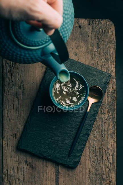 Verser le thé dans la tasse de main — Photo de stock