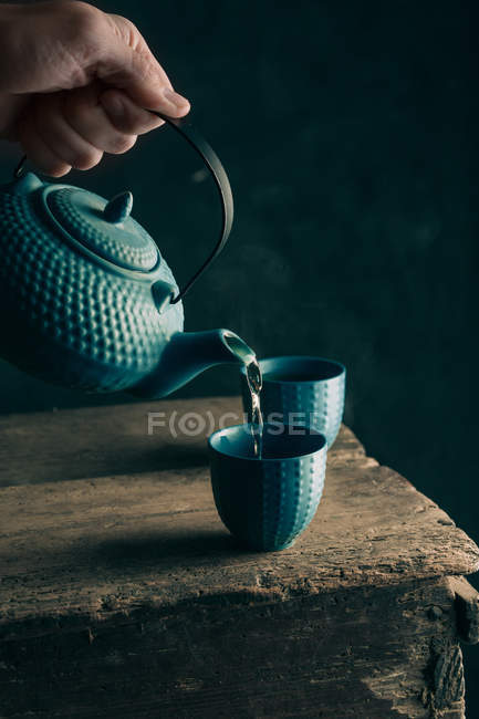 Hand pouring tea in cup — Stock Photo