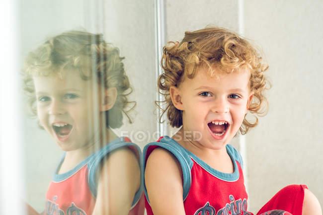 Menino sentado à janela — Fotografia de Stock