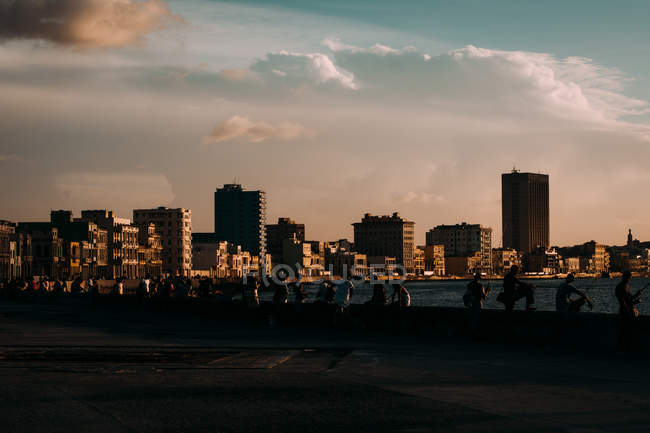 People relaxing on seafront with view of city at sunset under clouds, Cuba — Stock Photo