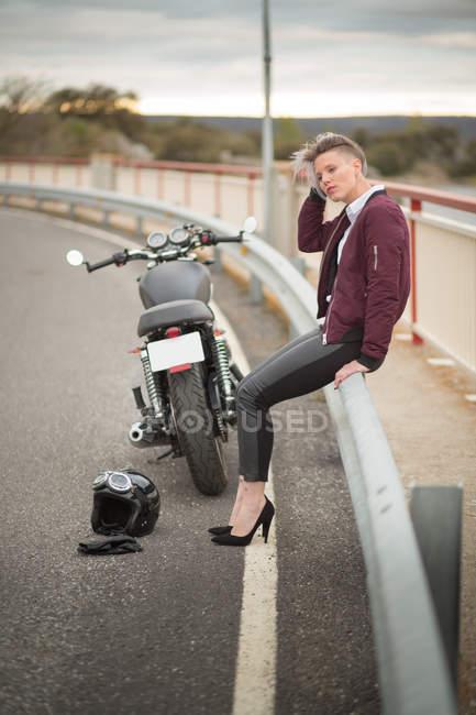 Woman sitting  next to motorbike — Stock Photo