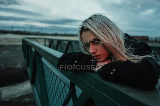 Woman leaning on fence in evening — Stock Photo