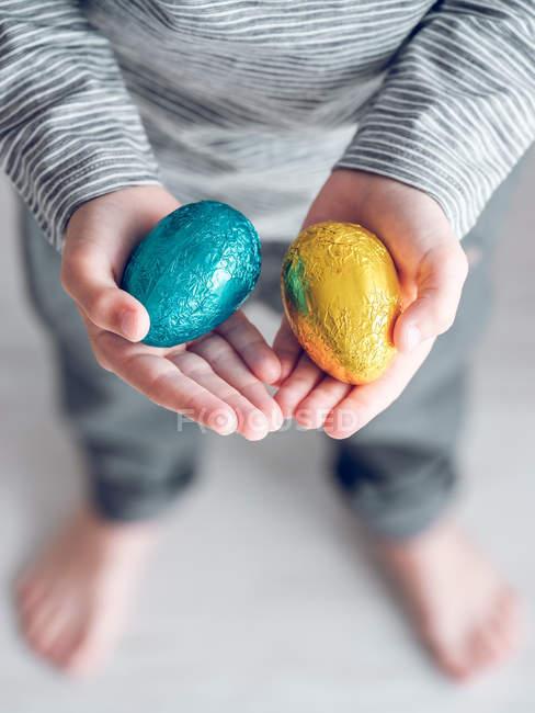 Vista cortada de menino irreconhecível segurando ovos de chocolate dourado e azul . — Fotografia de Stock