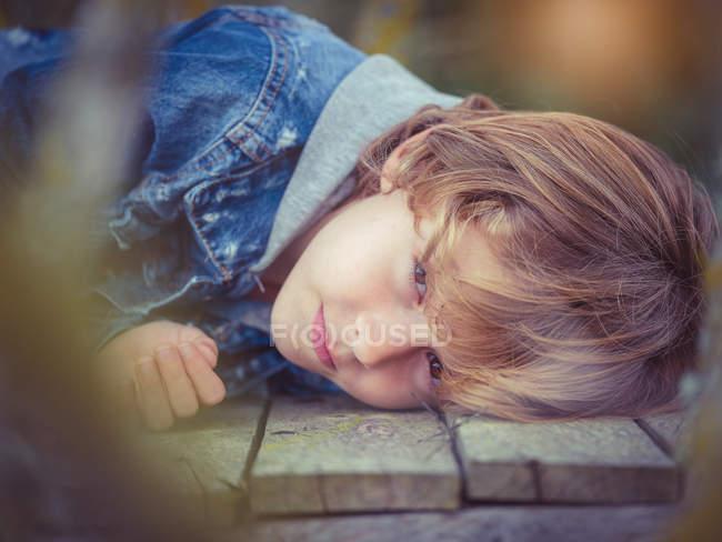 Мальчик, лежащий на борту — стоковое фото