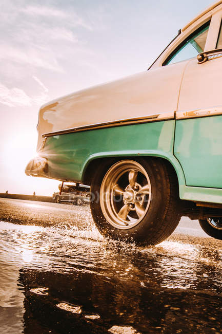 Close-up of shiny vintage blue and pink car driving on road and splashing water in puddle in backlit — Stock Photo