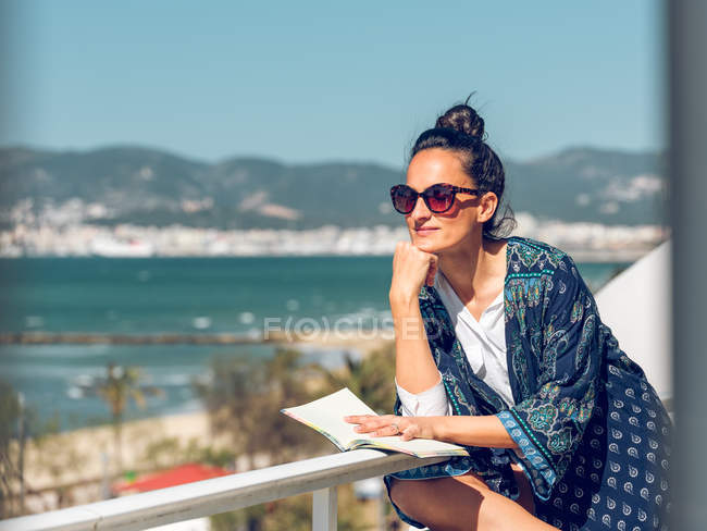 Young woman relaxing with book at balcony by seaside. — Stock Photo