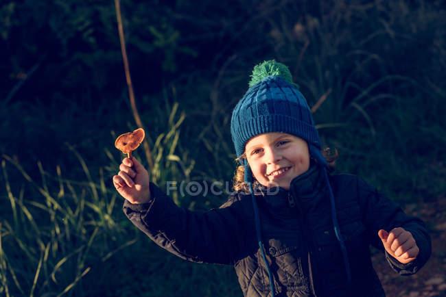Sorrindo menino mostrando cogumelo — Fotografia de Stock