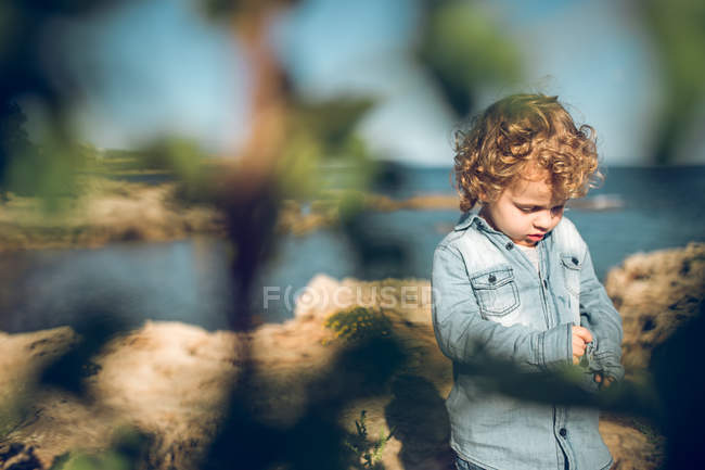 Ragazzo in piedi sulla costa — Foto stock