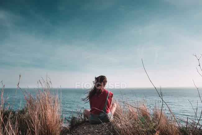 Mulher sentada e olhando para a paisagem marinha — Fotografia de Stock