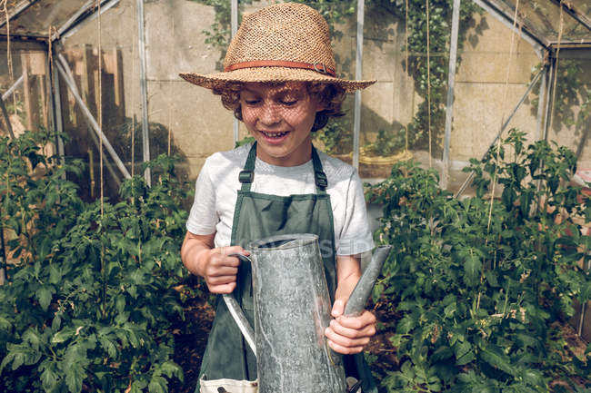Boy holding watering can in greenhouse — Stock Photo