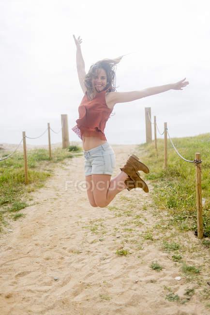 Mulher pulando no caminho arenoso — Fotografia de Stock