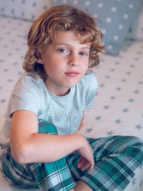 Menino encantador de pijama sentado na cama — Fotografia de Stock
