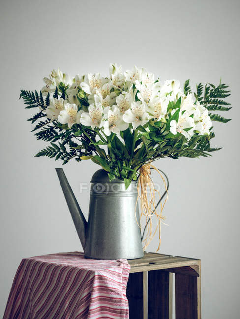 Bunch of flowers in watering can — Stock Photo