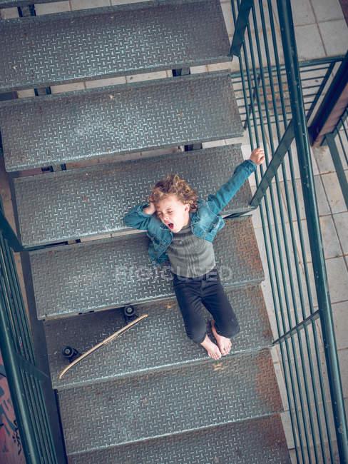 Menino deitado com skate nas escadas — Fotografia de Stock