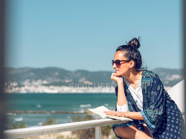 Junge Frau entspannt mit Buch auf Balkon am Meer. — Stockfoto