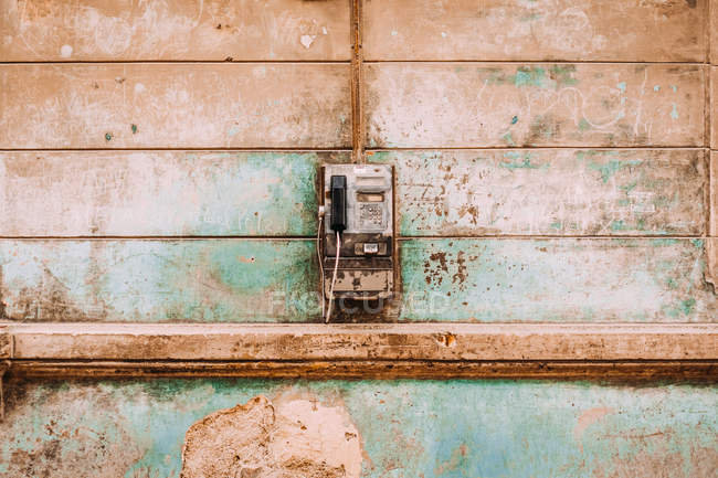 Old coin telephone hanging on shabby weathered exterior wall of building — Stock Photo
