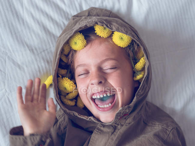 Boy in wreath of yellow flowers — Stock Photo