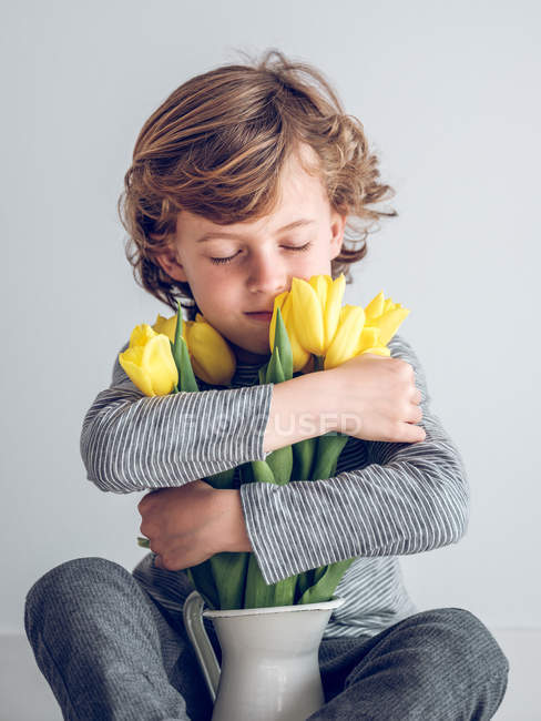 Elementary age boy with eyes closed sitting and embracing bunch of yellow tulips on gray background. — Stock Photo