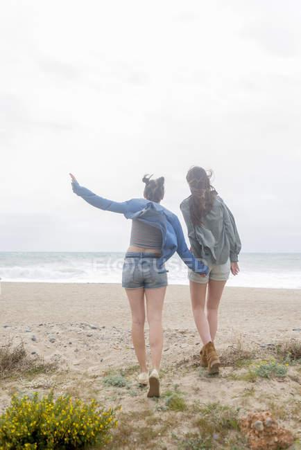 Female friends walking on beach — Stock Photo