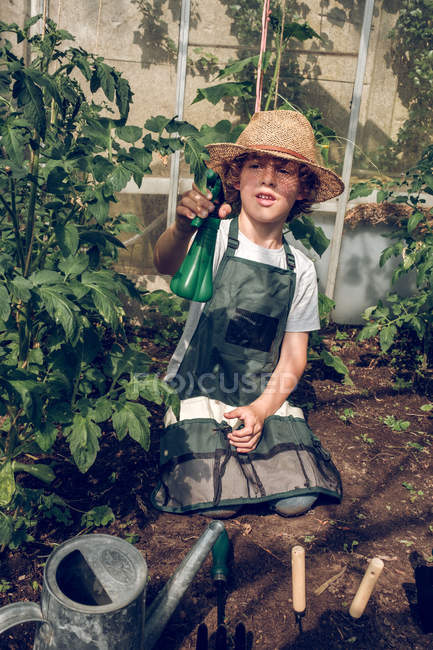Boy holding spray bottle in greenhouse — Stock Photo