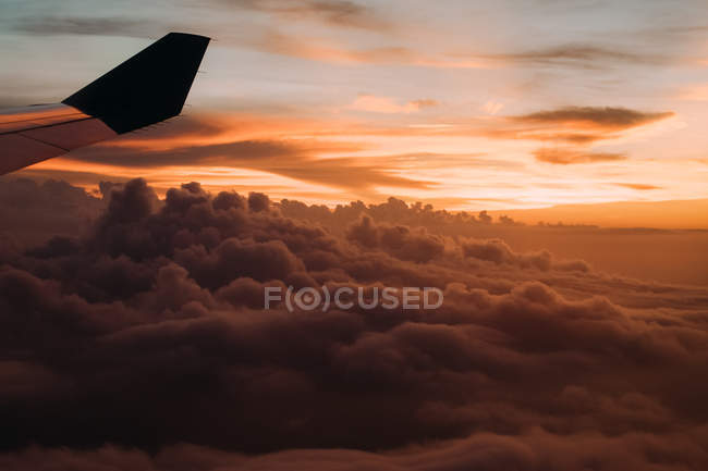 Dramatic sky with clouds and plane wing at sunset — Stock Photo