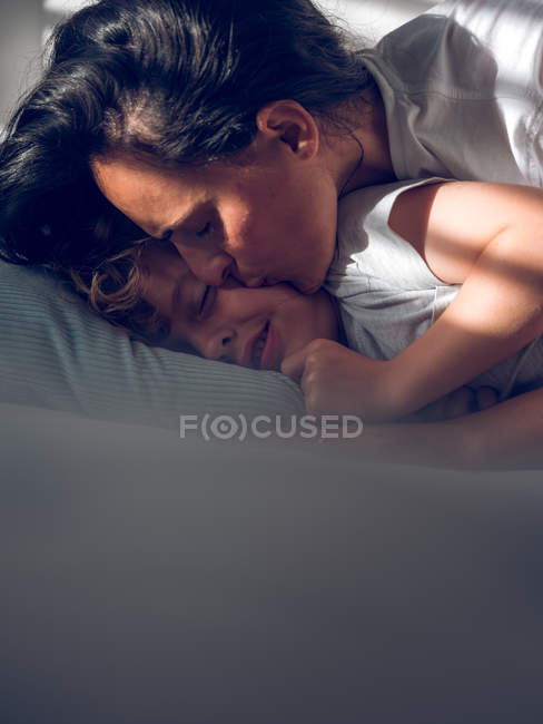 Mother kissing sleeping son — Stock Photo