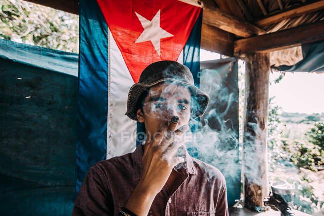 La Habana, Cuba - 1. Mai 2018: Mann in Hut Rauchen Dicke Zigarren stehen gegen Flagge Kubas in kleinen Hütte in der Sonne — Stockfoto