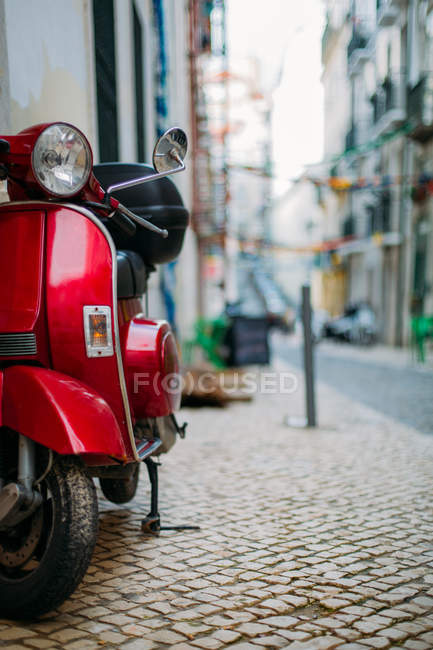 Red scooter parked on street — Stock Photo