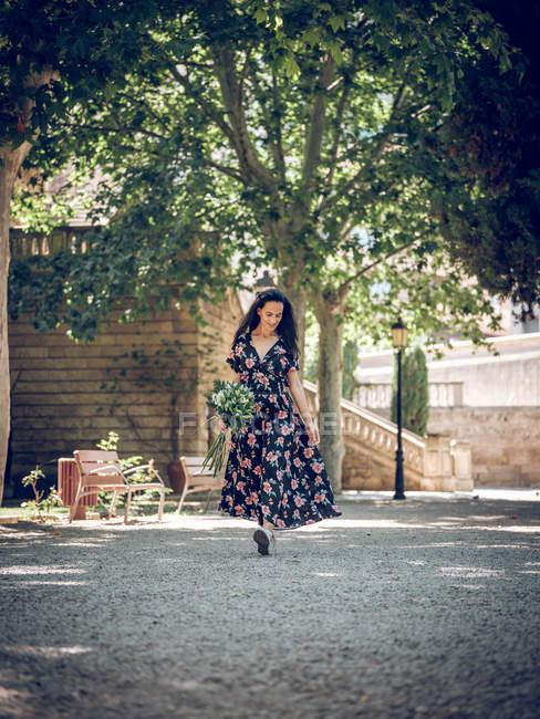 Mulher com buquê no parque ensolarado — Fotografia de Stock