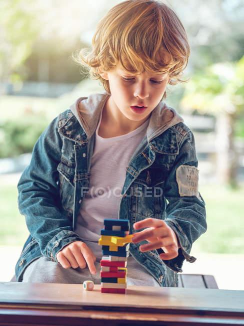 Garçon jouer avec des blocs de tour en bois — Photo de stock