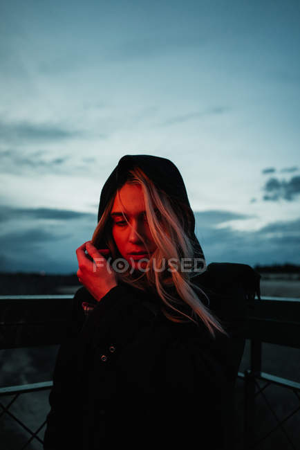 Blonde woman standing in dusk — Stock Photo