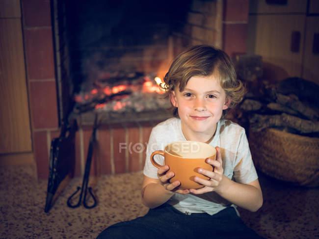 Fröhlicher Junge sitzt mit Tasse am Kamin — Stockfoto