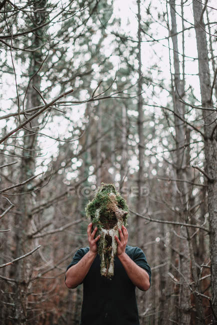 Tourist holding skull with moss — Stock Photo