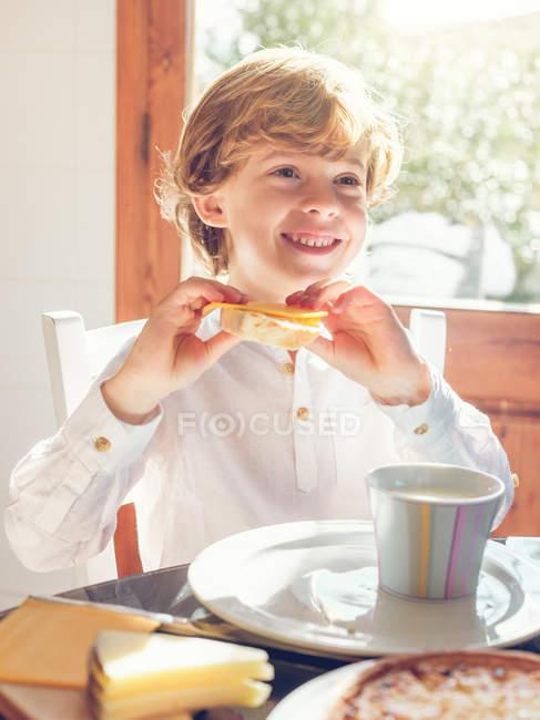 Ragazzo seduto e in possesso di pane con formaggio — Foto stock