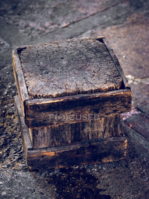 Dirty wooden cube placed on floor of factory. — Stock Photo