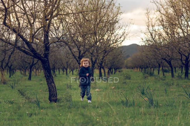 Garçon en cours d'exécution sur une prairie ensoleillée — Photo de stock