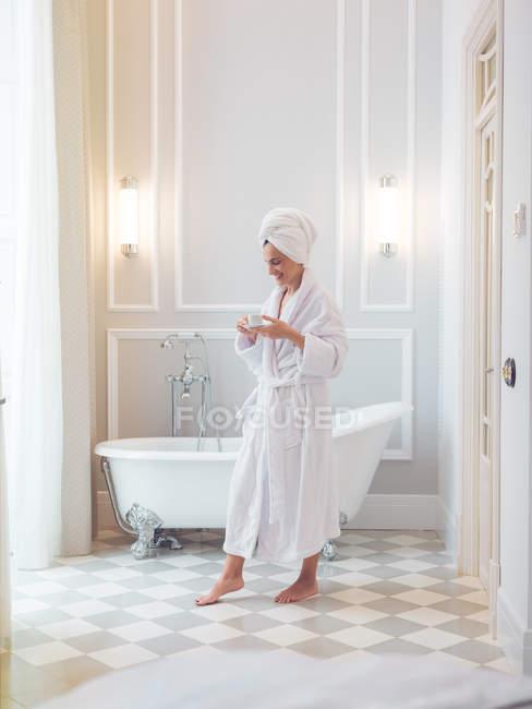 Женщина в халате с колбой в ванной комнате — стоковое фото