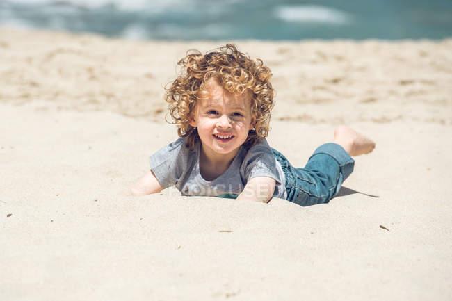 Menino deitado na praia — Fotografia de Stock