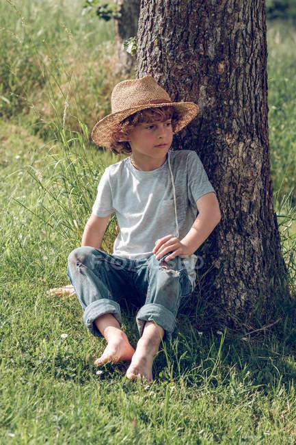 Босоногий мальчик сидит под деревом — стоковое фото