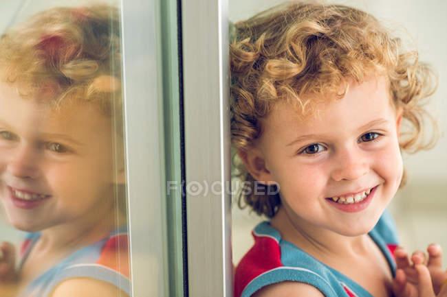 Smiling boy at window — Stock Photo