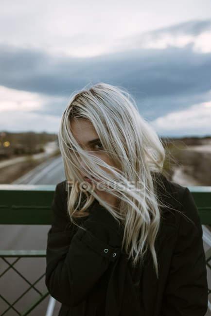 Blondine steht auf Fußgängerbrücke — Stockfoto