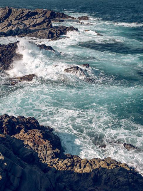 Onde che si infrangono sulle rocce — Foto stock