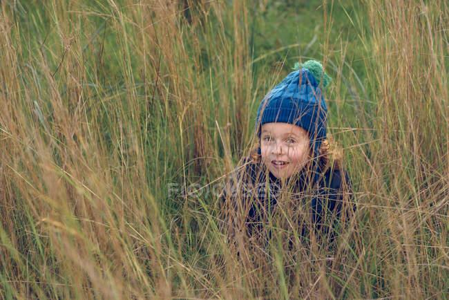 Маленький мальчик сидит в траве — стоковое фото