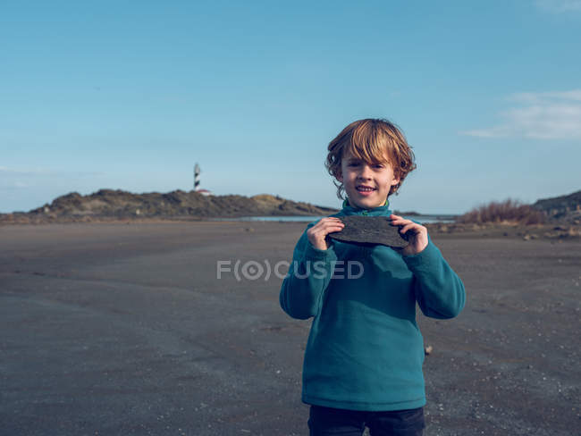 Cheerful boy standing with stone — Stock Photo