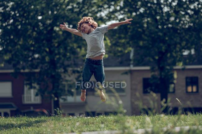 Garoto excitado pulando acima da grama — Fotografia de Stock